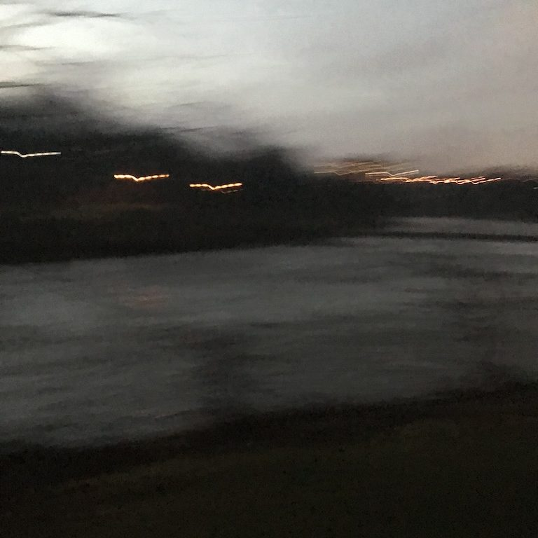 A blurry photo of the river at dusk in dark greys and blues, with lights across the river smeared.