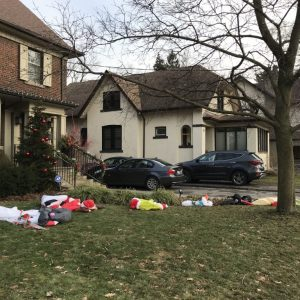 A photo of a lawn in front of a brown house with collapsed inflatable Santas, snowmen and other winter characters on the grass.
